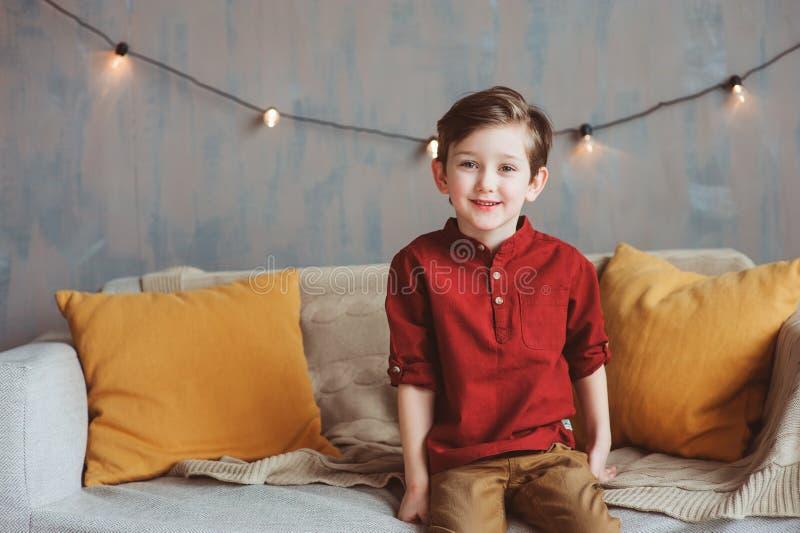 salowy portret szczęśliwy przystojny elegancki dziecko chłopiec obsiadanie na wygodnej leżance zdjęcie stock