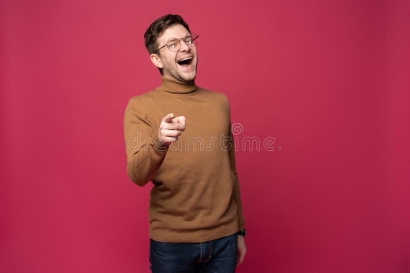 Salowy strzał rozochocony mężczyzna w widowiskach i przypadkowych ubraniach wskazuje szczęśliwie przy tobą, wybiera współzawodnic zdjęcie royalty free