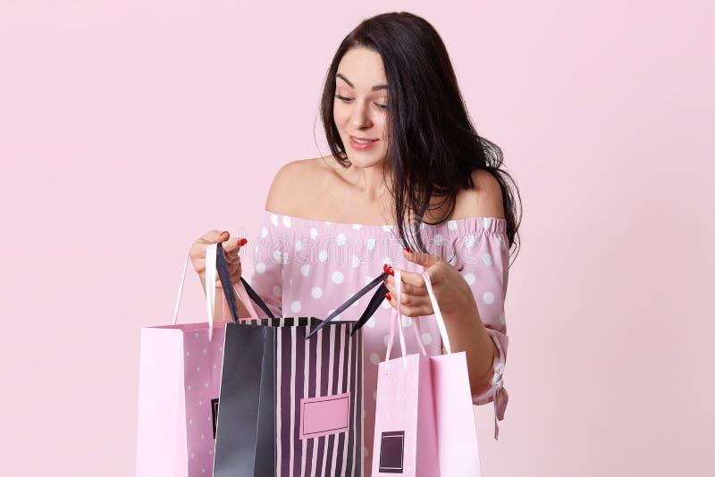 Salowy strzał ładni kobiet spojrzenia przy prezentem ciekawie zdojest, otrzymywa teraźniejszość od przyjaciół na urodziny, jest u obrazy stock