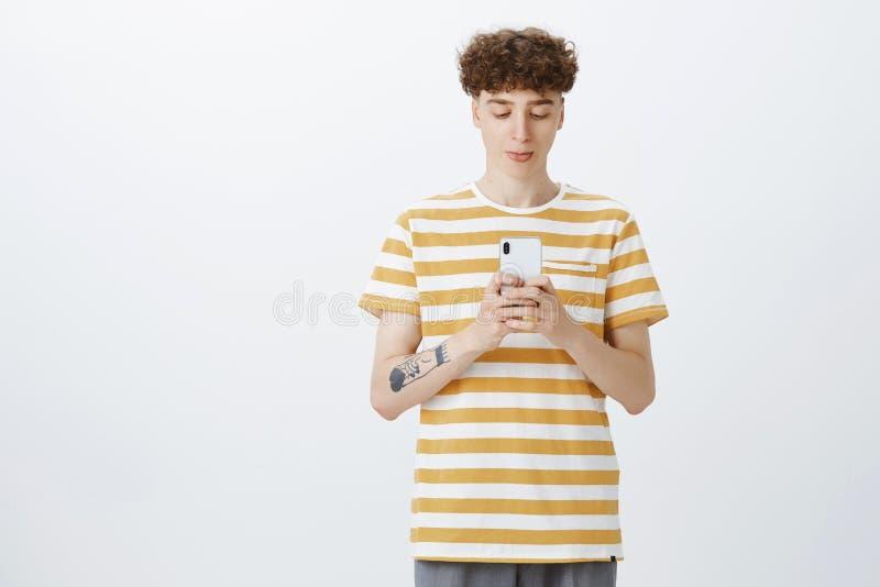 Salowy strzał śmieszny nerdy przystojny facet pouting jak być z podnieceniem z kędzierzawą fryzurą i tatuaże bawić się smartphone fotografia royalty free