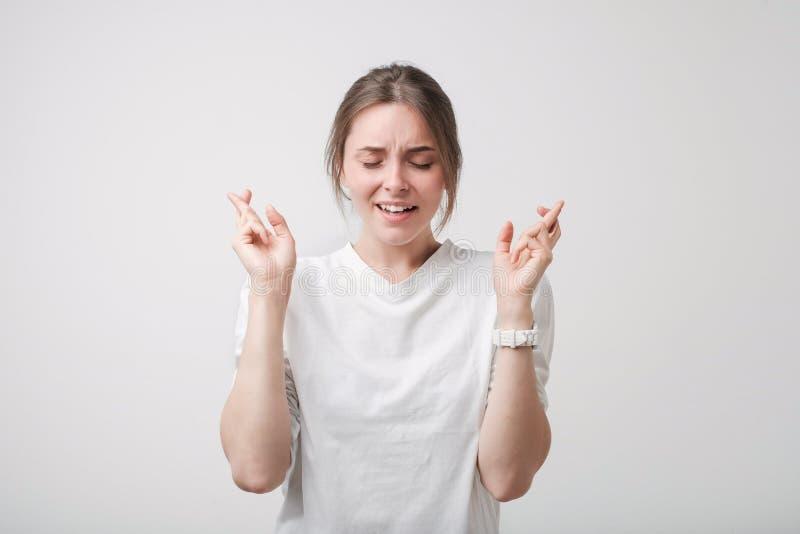 Salowy strzał atrakcyjna europejska dziewczyna w białej koszula excited, zabobonny spojrzenie, utrzymuje palce krzyżujący obraz stock