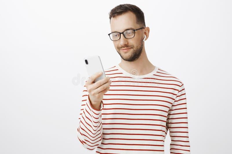 Salowy strzał atrakcyjny zrelaksowany europejski mężczyzna w szkłach, trzymający smartphone, podnoszący piosenkę słuchać, będący  fotografia stock