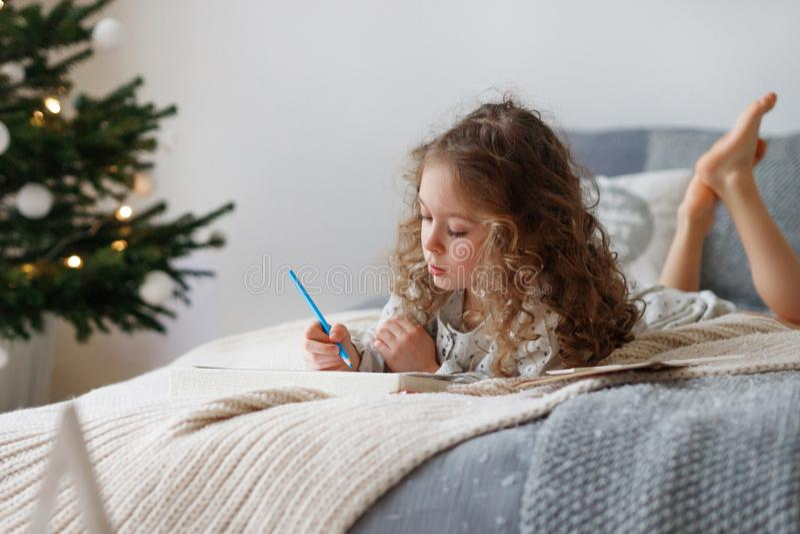 Salowy strzał baczna dosyć mała dziewczyna pisze liście Święty Mikołaj przed bożymi narodzeniami, myśleć jaki teraźniejszość ona zdjęcia stock