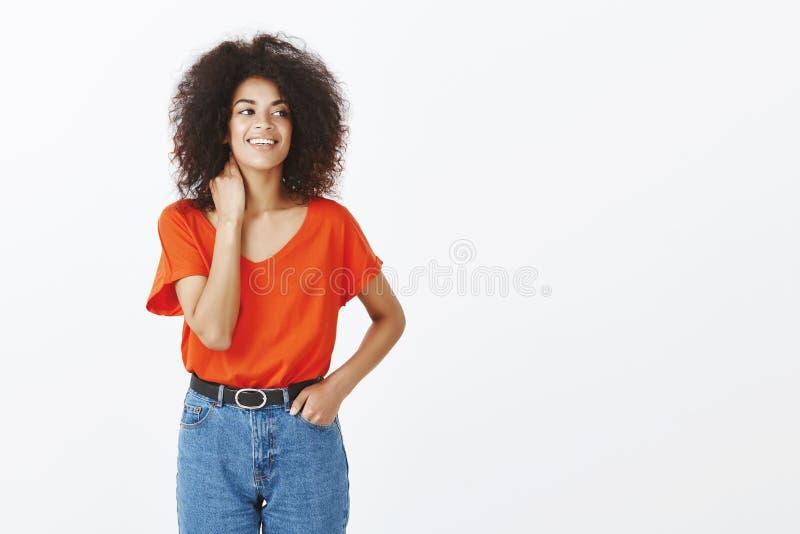 Salowy strzał beztroska atrakcyjna ciemnoskóra kobieta z afro fryzury wzruszającą szyją i patrzeć dobro z zdjęcie royalty free