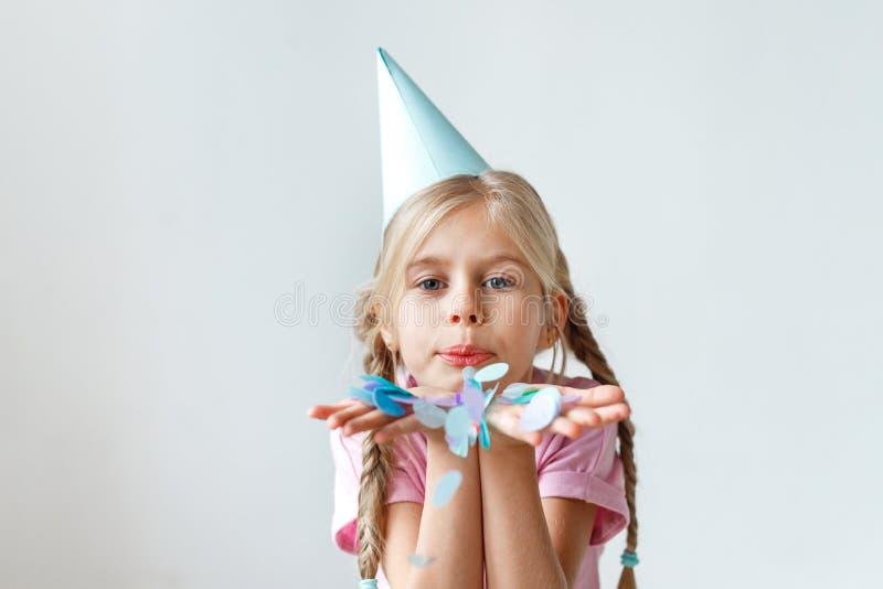 Salowy strzał dosyć mały dzieciak z długimi pigtails, jest ubranym szyszkowego kapelusz na głowie, dmucha colourful prześcieradło obrazy stock