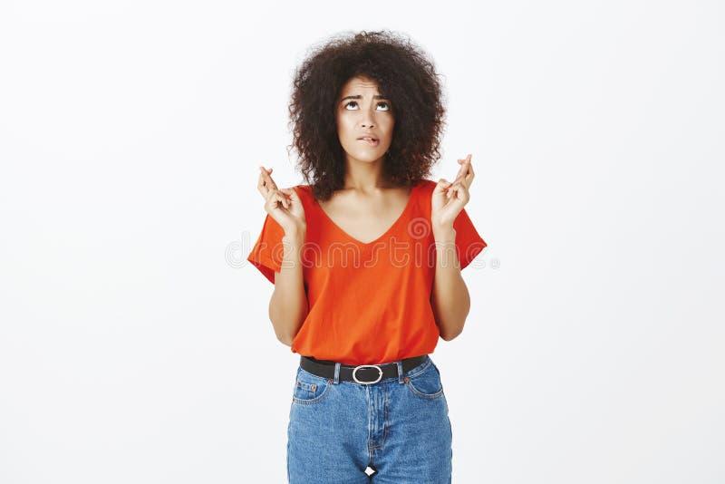 Salowy strzał intensywny zmartwiony żeński uczeń z afro fryzurą, przyglądającą wargą stoi z krzyżujący, up i zjadliwą, zdjęcia stock