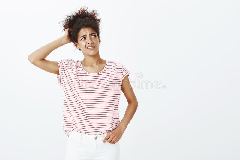 Salowy strzał niepewna atrakcyjna z włosami kobieta w pasiastej koszulce, chrobotliwym plecy, głowa i marszczyć brwi podczas gdy fotografia stock
