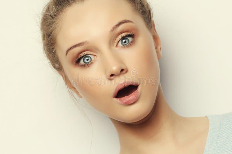 Salowy strzał odurzona szokująca blondynki kobieta utrzymuje usta szeroko otwiera, spojrzenia przy kamerą, jest ubranym przypadko zdjęcia stock