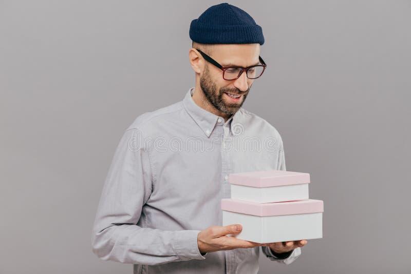 Salowy strzał przystojny nieogolony mężczyzna z brislte trzyma dwa pudełka, szczęśliwego otrzymywać teraźniejszość od przyjaciela obraz stock