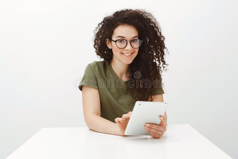 Salowy strzał siedzi przy bielu stołem i wyszukuje w sieci przez cyfrowej pastylki ładna brunetka w czarnych szkłach, zdjęcia royalty free
