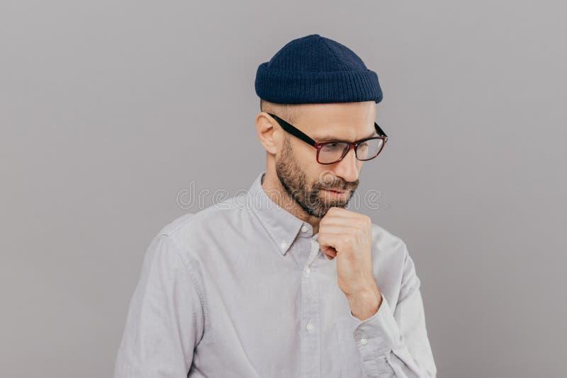 Salowy strzał skoncentrowany mężczyzna trzyma podbródek i skupiający się puszek, być w głębokim w myślach, myśleć o nowatorskim p fotografia stock
