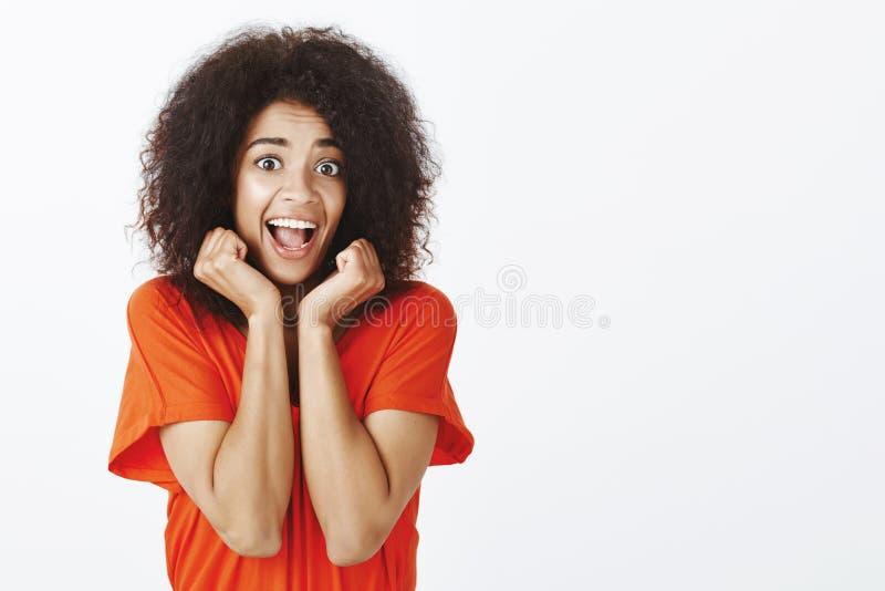 Salowy strzał szczęśliwy energiczny ciemnoskóry kobieta model z afro fryzurą, trzyma wręcza blisko twarzy i krzyczeć od obrazy royalty free