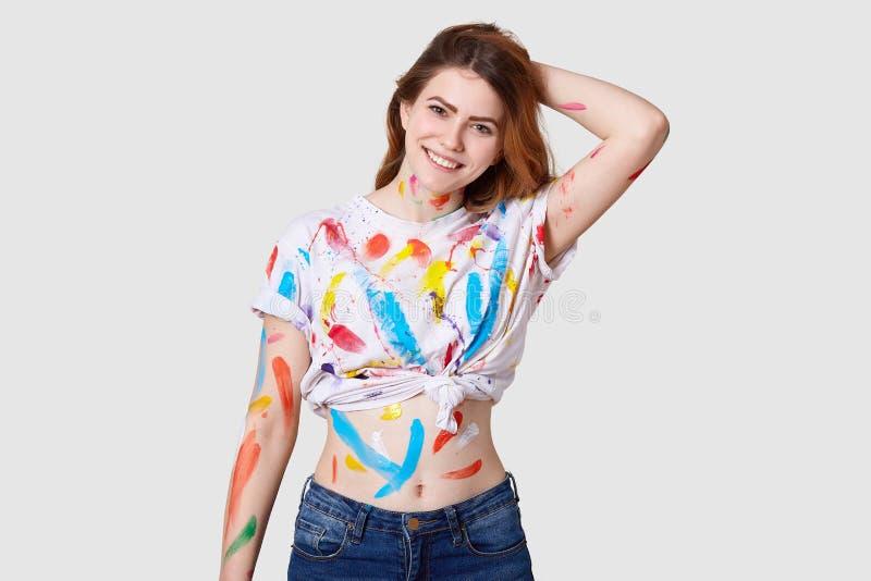 Salowy strzał szczęśliwy Europejski żeński malarz brudnego ciało i biała t koszula z colourful farbami, pokazuje brzucha, utrzyma fotografia royalty free
