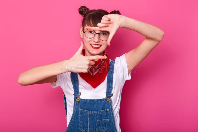 Salowy studio strzał rozochocony energiczny żeński seansu znak robić fotografii, stawiający ręki przed ona, ono uśmiecha się zdjęcie royalty free