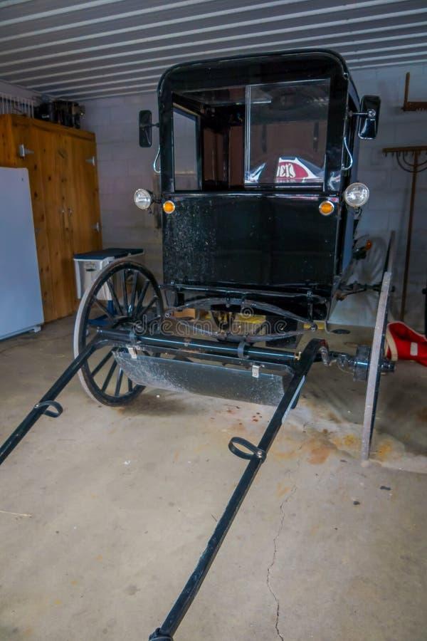 Salowy widok Amish czerni fracht lub powozik parkujący wśrodku garażu dom w Lancaster okręgu administracyjnym obraz stock