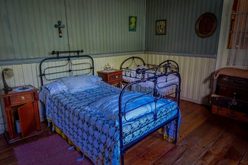 Salowy widok kruszcowy łóżko z dwa piedestału drewnianym stołem wśrodku Chonchi muzeum, darujący rodzinami Chonchi obrazy royalty free