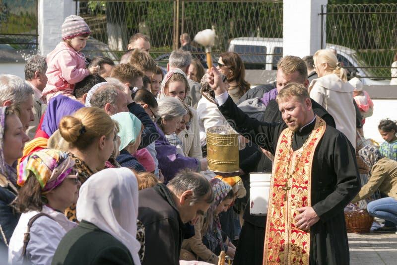 Salpicón ortodoxo del sacerdote que el agua santa en Pascua se apelmaza foto de archivo libre de regalías