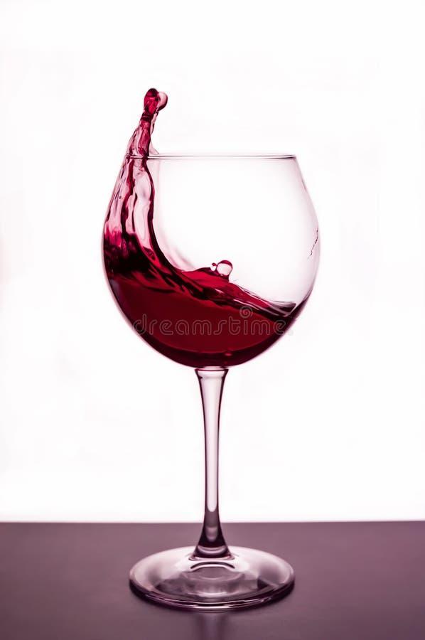 Salpica del vino tinto en una copa fotos de archivo libres de regalías