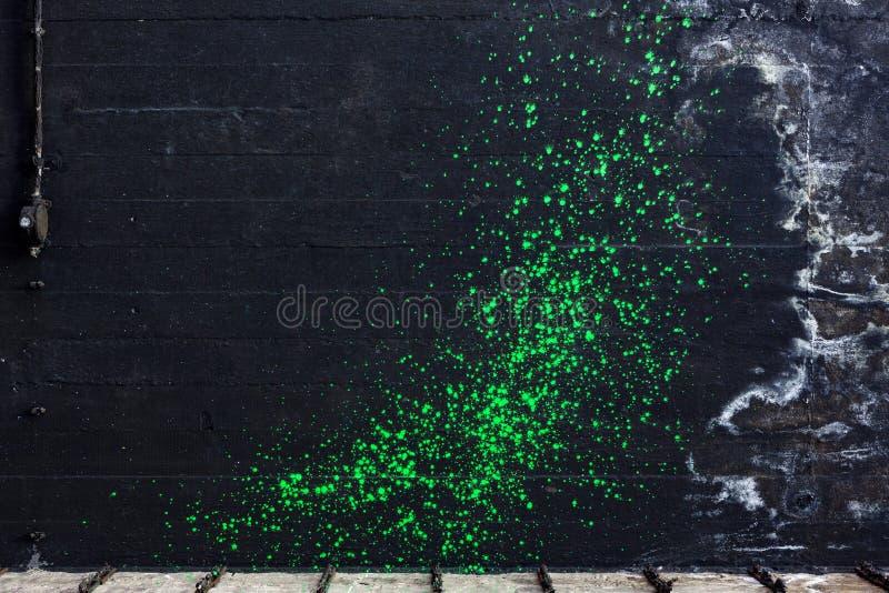 Salpicadura verde del dolor en el muro de cemento negro imagen de archivo libre de regalías