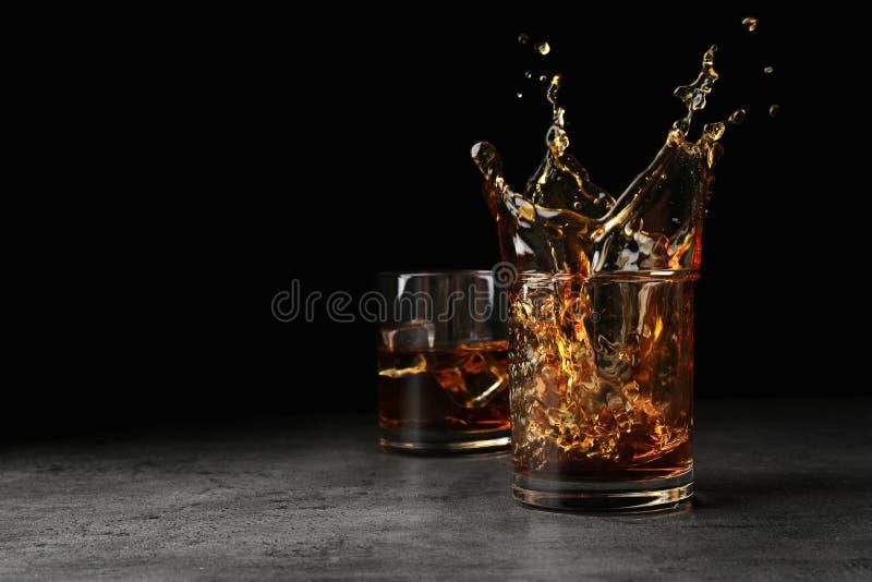 Salpicar el whisky de oro en vidrio con los cubos de hielo en la tabla imagenes de archivo