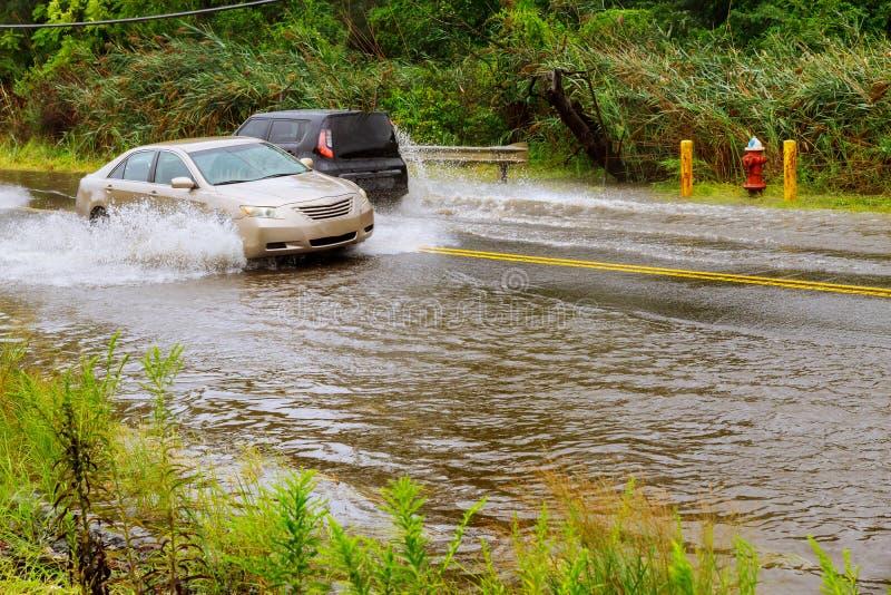 Salpique en coche como pasa a través del agua de inundación después de fuertes lluvias de la tormenta del huracán de Harvey imagenes de archivo
