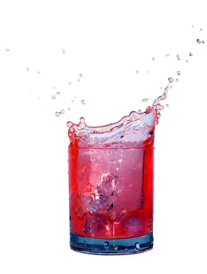 Salpique en un vidrio de líquido rojo aislado en blanco fotografía de archivo libre de regalías