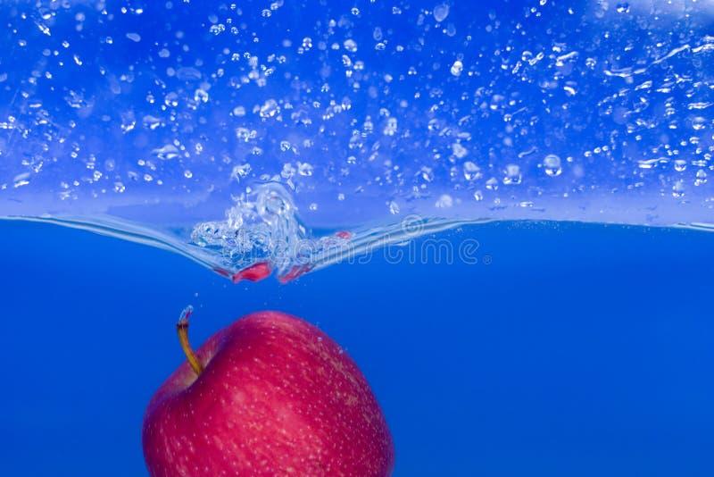 Salpique-serie: manzana roja con el fondo azul fotos de archivo libres de regalías