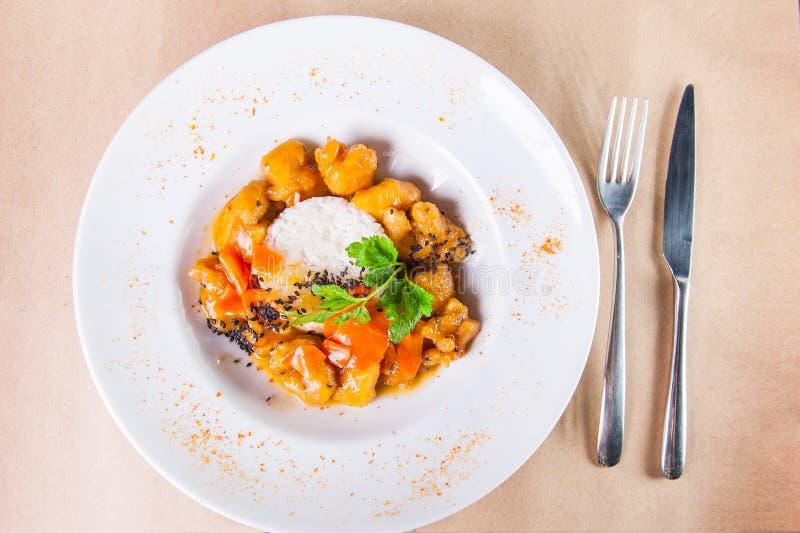 Salsa agrodolce del pollo cinese di vista superiore, servita con riso nel piatto bianco con la coltelleria sui precedenti della c fotografia stock