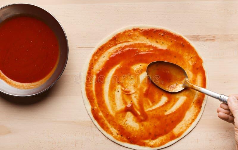 Salsa al pomodoro di diffusione del cuoco unico sulla base della pizza immagini stock libere da diritti