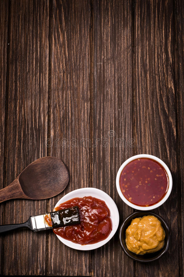 Salsa barbecue sopra la tavola rustica di legno del granaio fotografie stock libere da diritti
