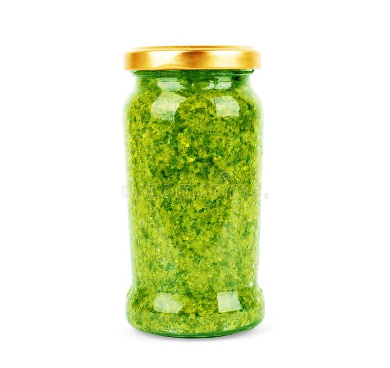 Salsa casalinga di pesto del basilico in barattolo di vetro su fondo bianco fotografia stock