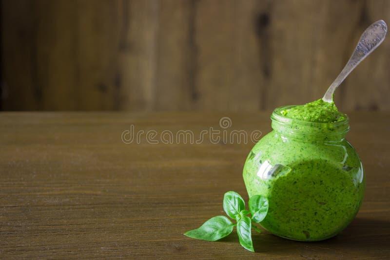 Salsa casalinga di pesto in un barattolo con basilico sopra la tavola di legno fotografia stock libera da diritti
