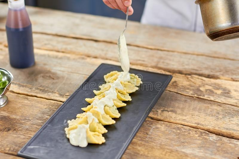 Salsa cremosa bianca di versamento della mano del cuoco unico sui ravioli immagini stock