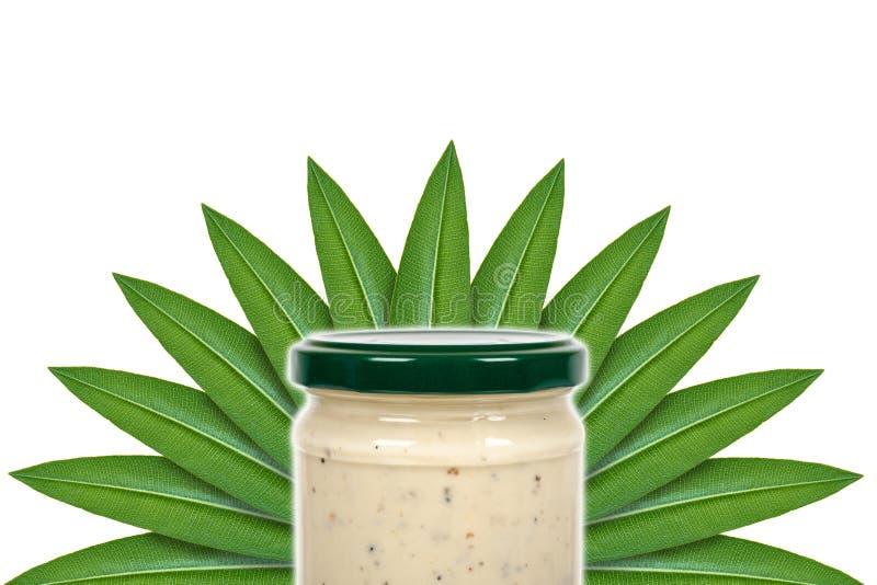 Salsa cremosa con la trufa para las pastas en el tarro de cristal en el fondo de hojas verdes Aislado en blanco imagen de archivo