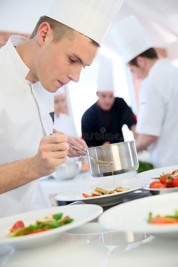 Salsa de colada del aprendiz del cocinero de los jóvenes en plato foto de archivo libre de regalías