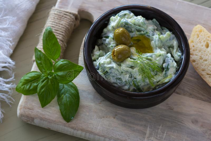 Salsa de la inmersión o tzatziki griego e ingredientes del vestido adornados con aceite y albahaca de oliva en la tabla de madera imagen de archivo