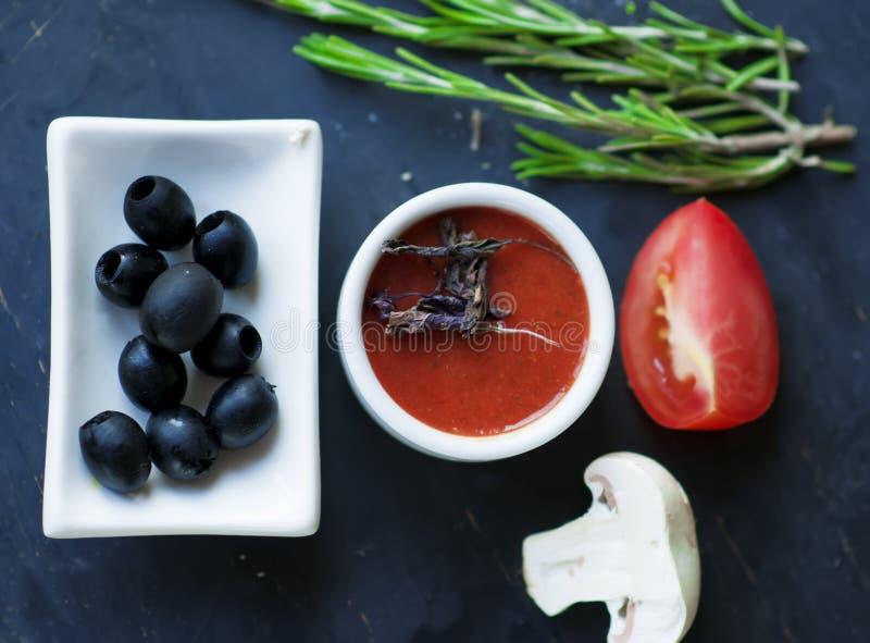 Salsa de tomate con albahaca seca y aceitunas negras imagen de archivo libre de regalías