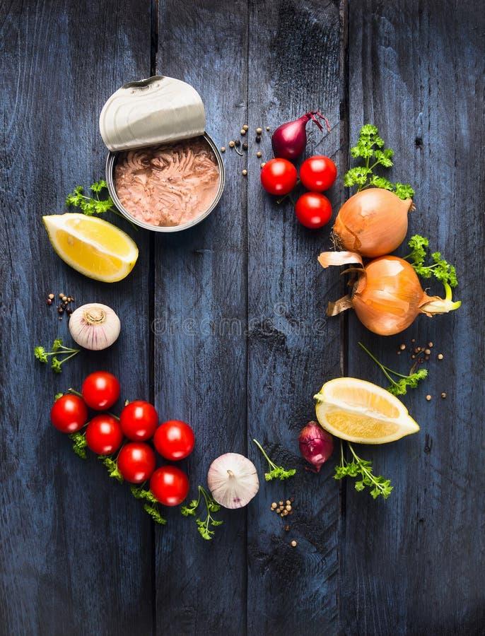 Salsa de tomate con el ingrediente de los pescados de atún con la hierba, las especias y el limón en fondo de madera azul fotografía de archivo libre de regalías
