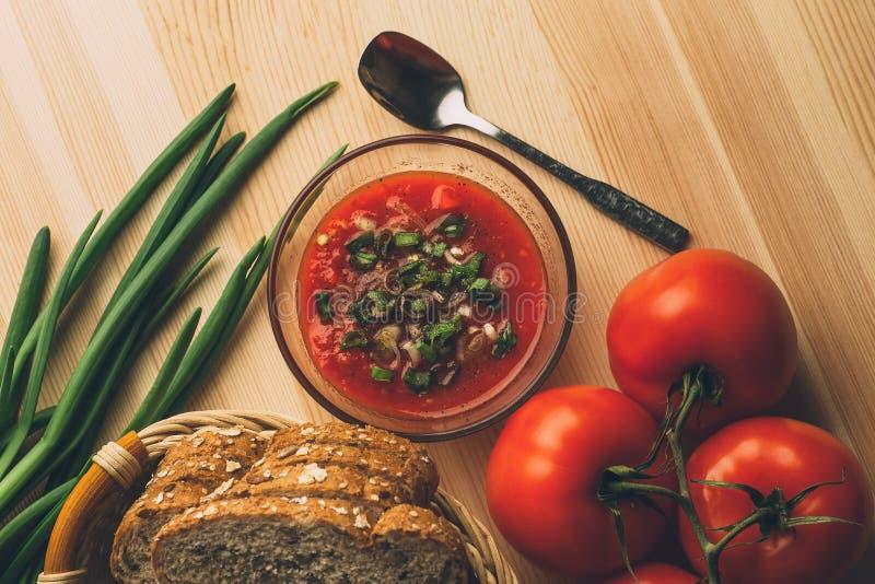 Salsa de tomate en el bol de vidrio, pan fresco, cebolla en la tabla de madera, ingredientes de la salsa para la comida sana vege fotografía de archivo