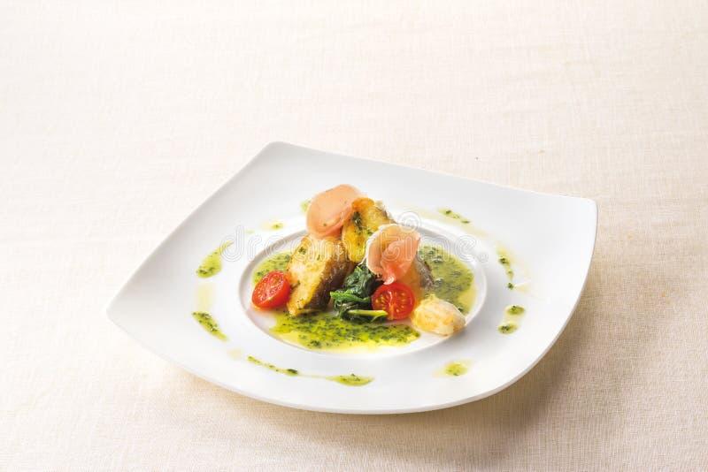 Salsa del burro del basilico di Poiret del pesce bianco sul backgroun bianco del piatto fotografia stock libera da diritti