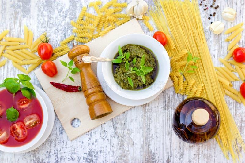 Salsa del pesto de la albahaca, salsa de tomate e ingredientes para la comida sana, deliciosa foto de archivo libre de regalías