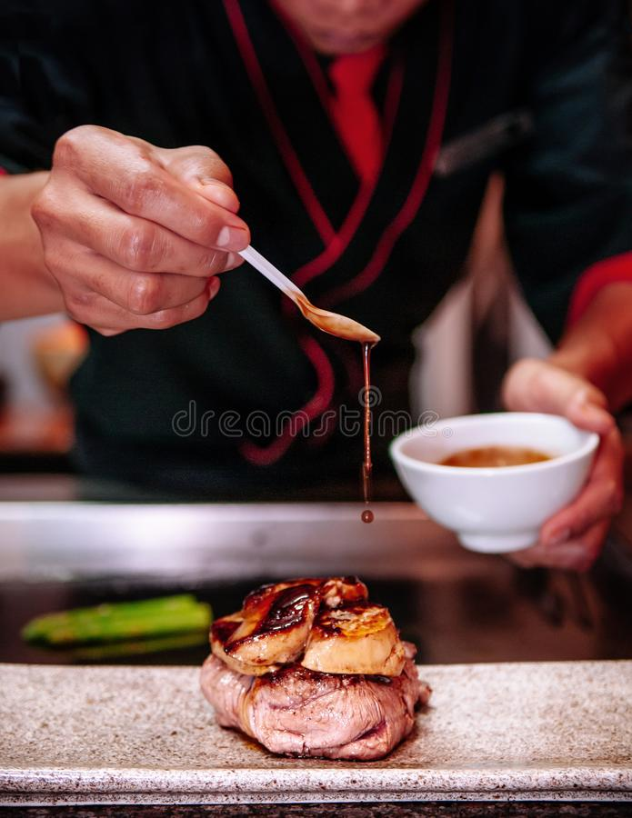 Salsa del sugo della sgocciolatura sulla bistecca del mignon di raccordo con il foie gras immagine stock