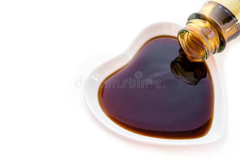 Salsa dell'ostrica nella forma bianca del cuore della tazza fotografia stock
