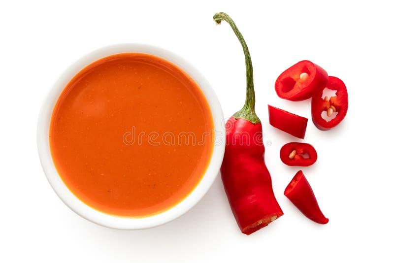 Salsa di peperoncini rossi dei peri dei peri in una ciotola ceramica bianca accanto del tagliare ad un peperoncino isolato su bia fotografia stock libera da diritti