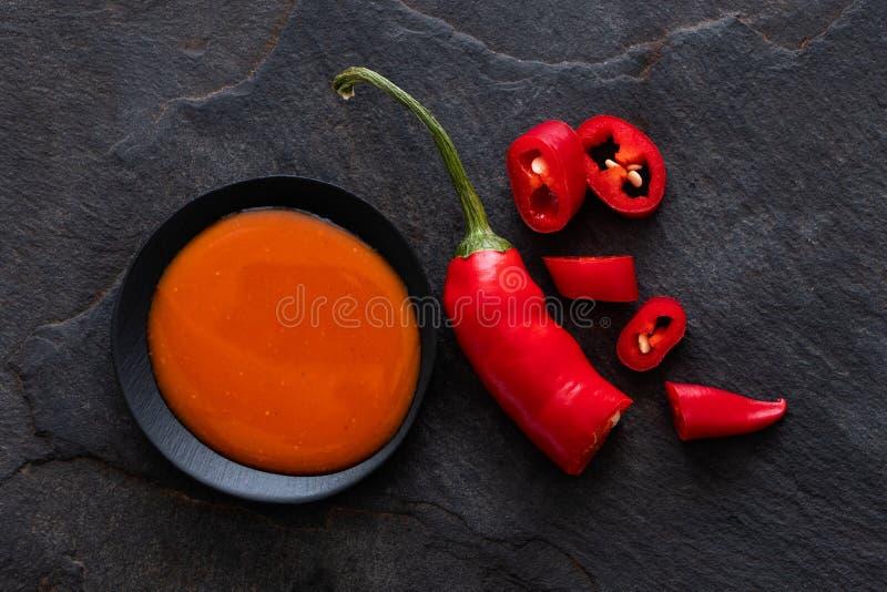 Salsa di peperoncini rossi dei peri dei peri in una ciotola ceramica nera accanto del tagliare ad un peperoncino sull'ardesia ner immagine stock