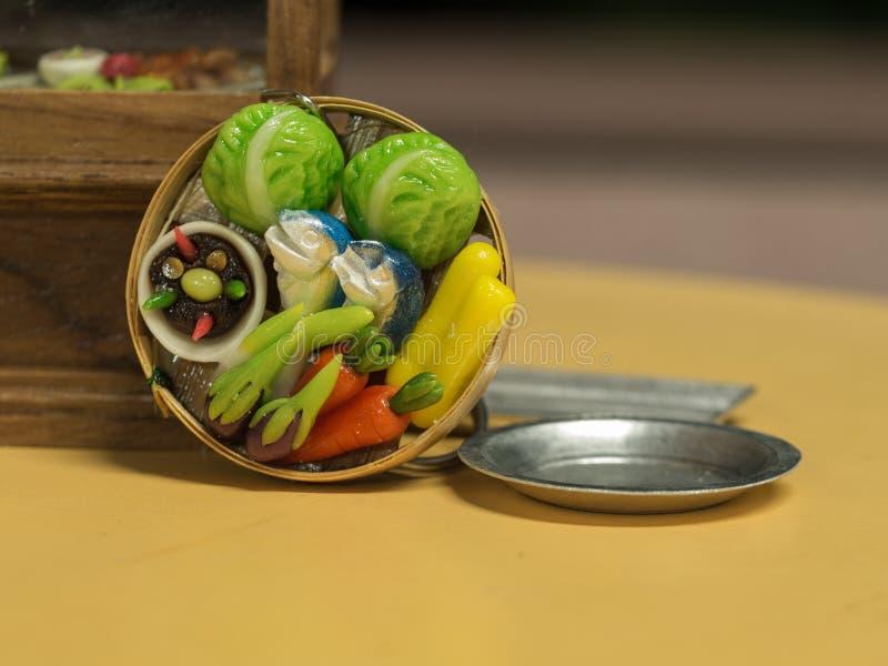 Salsa di peperoncino rosso e giocattoli minuscoli di verdure immagini stock