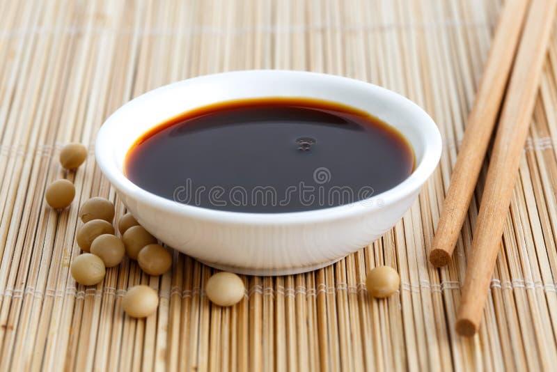 Salsa di soia in ciotola bianca sulla stuoia di bambù con i bastoncini e la caduta immagini stock libere da diritti
