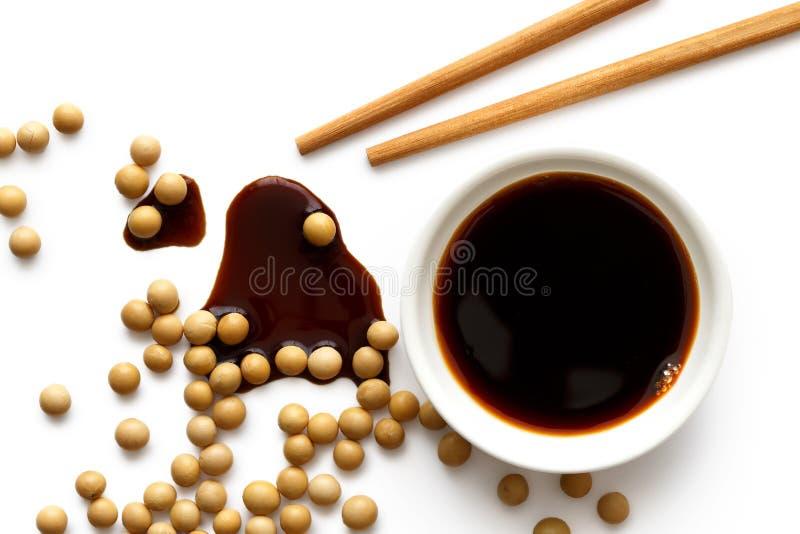 Salsa di soia in ciotola ceramica bianca su bianco da sopra con di legno immagini stock