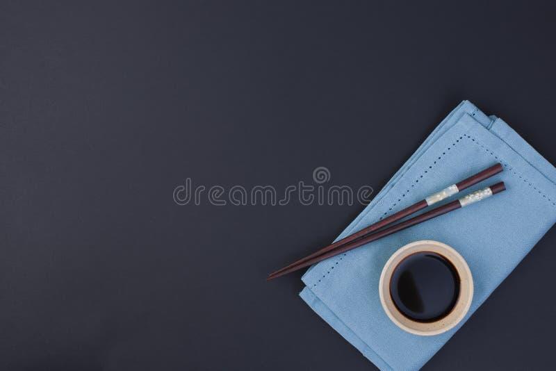 Salsa di soia e bastoncini per alimento cinese Tovagliolo blu e fondo nero Posto per testo fotografie stock