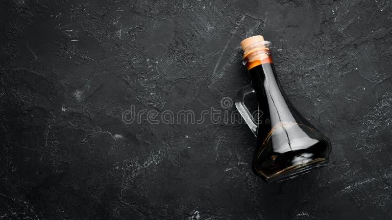 Salsa di soia su un fondo di pietra nero immagine stock